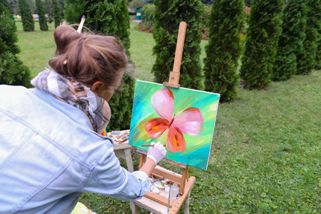 ou: Young girl European appearance looks at drawing of Multicolored butterflies, which painted with oil paints and estimates finalizing remaining details. Stands near wooden easel with brush in hands on background art materials and coniferous trees in park ou