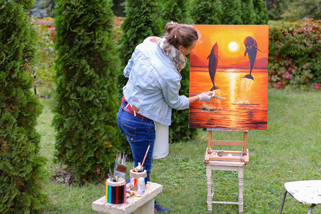 smeared: Pretty attractive artist finishes painting which depicts dolphins jumping out of  water on orange background, stands with back to photographer and behind wooden easel, holds palette smeared in paint in large green park day outdoors.Girl dressed in red swe