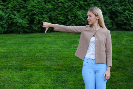 Slender blonde curves and shows gesture Bad grieved and shows evaluation of product, does not recommend fitness club or restaurant. Women with long blonde hair dressed in bright blouse, beige jacket and blue pants, standing on background of green grass