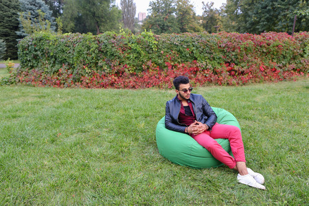Arabian Young Man Sitting and Resting From City Bustle in Soft Green Chair and Looks Around. Handsome Guy Has Dark Hair and Black Beard and Wearing Maroon Shirt Over Black Leather Jacket and Bright Pink Jeans and White Sneakers Accessories From Sunglasses Stock Photo