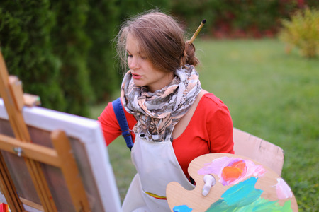 Pretty attractive artist begins to or finishes drawing sitting right in front of to photographer and behind wooden easel, holds palette smeared in paint in large green park day outdoors.Girl with brown hair collected in beam dressed in red jacket, dark de Stock Photo