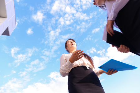 Two attractive successful woman, young office workers, businessmen, students communicate, make deal, shake hands, discuss working moments, versed in reports, kept in hands documents and view them, smiling and posing against sky near business center in ope Zdjęcie Seryjne