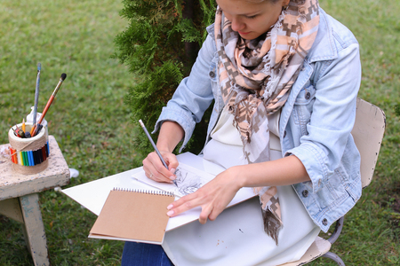 Contemporary Artist Works on Facial Contour of Depicted on Portrait Unknown Girl, Draws Sketch of Fictional Head, Prepares Gift For Friend. Woman Located in Park Outdoors in Background Stands Bench With Colors and Additional Art Materials. Artist Dressed  Stock Photo