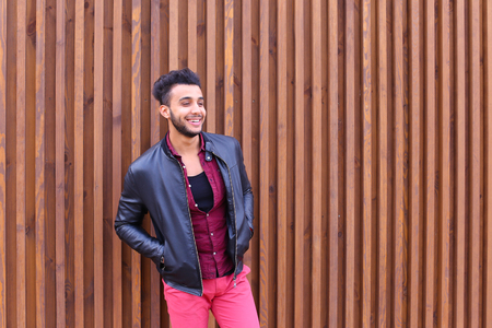 Charismatic Young Businessman Muslim Man Comes Closer to Camera, Smiles and Poses For Camera on Photographer, Shows Gestures, Laughs, Advertises Clothing on Wooden Panel Background Stairs Outdoors. Stylish Young Man With Dark Hair and Sunglasses Dressed i