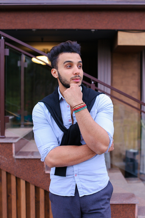 where to go: Serious student of Arabic businessman about something and remembers thinking, posing for catalog of brand of mens clothing, arranged meeting with friends, thinking where to go have fun on weekends. Handsome Muscular Guy Dressed in Black Classic Trousers,