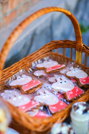 On photo depicts pink gingerbread with pattern Peppa pig, cartoon character, which sealed in transparent cellophane and stacked in brown wicker basket, which is located near other treats on table outdoors. Concept birthday, childrens holiday, holiday tabl