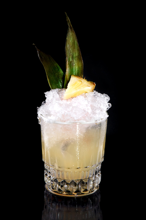 pale color: Exotic alcoholic or non-alcoholic refreshing drink with pineapple syrup and  pale yellow color, decorated on top with  slice of pineapple and leaves in  transparent glass beaker on  black background.  Concept of soft and alcoholic drinks, refreshments or