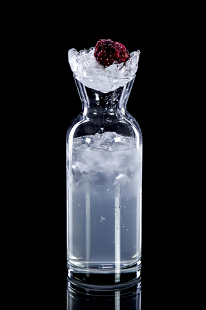 Cool refreshing alcoholic or non-alcoholic cocktail drink in long transparent bottle with  clear liquid or syrup and ice topped with raspberries on  black background.  Concept of soft and alcoholic drinks, refreshments or advertising quench thirst, beauti
