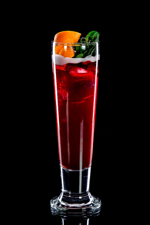 Alcoholic or non-alcoholic cocktail in  long, high and narrow transparent glass with  dark red liquid and syrup topped with orange slices and mint on  white prosloke that separates drink and decoration on  black background.  Concept of soft and alcoholic  Stock Photo