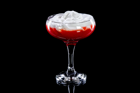 Alcoholic or non-alcoholic cocktail with whipped cream on  top layer and  berry liquid in  bottom layer in  long, high-transparent glass for  black background.  Concept of soft and alcoholic drinks, refreshments or advertising quench thirst, beautiful des