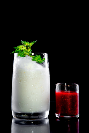 Large glass of milk or cream cocktail with alcohol or alcohol-free white top decorated with sprig of green grass and small shot of strawberry mix kontsentrirovonogo in transparent glass dish on black background. Concept of soft and alcoholic drinks, r