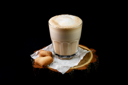 Flavored coffee beverage, latte or American with  glass of milk in  transparent glass. Glass is  white transparent paper lying next to  cookies in  heart shape on  wooden round stand on  black background.  Concept of light coffee drinks and  nice flow, an
