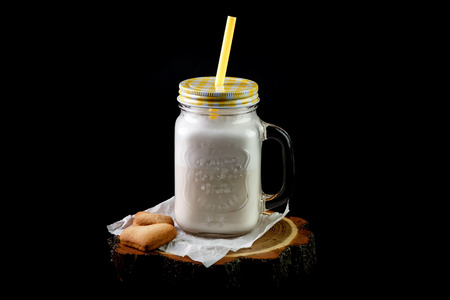 Milkshake in  glass transparent bank mug with lid and straw standing on  white transparent paper lying next to  cookies in  heart shape on  wooden round stand on  black background.  Concept of light coffee drinks and  nice supply of milk shakes, and enjoy Stock Photo