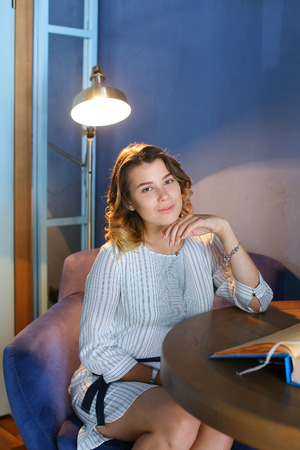 sitt: Young adult attractive confident female girl woman looks at camera and smiles, holds hand near face and sits in purple chair at table on background of gray lighted lamp and blue walls in beautiful stylish modern restaurant. Girl with blond curly hair sitt