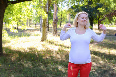 Gorgeous Young Adult Woman in Family Way of European Appearance Decided to go Outside and Get Some Fresh Air, Stretching and Warming up in Green Sunny Park Outdoors in Daytime. Female With Blonde Hair Braided in Braid in Front Dressed in White Blouse With