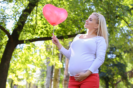 position d amour: Marvelous Young Adult Lady With Child of European Appearance Enjoying Sunny Day, Cute Smiles, Poses and Rises up Pink Ballons in Shape of Heart in Green Park Outdoors in Daytime. Female With Blonde Hair Braided in Braid in Front Dressed in White Blouse Wi Banque d'images