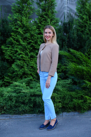 gi: Women with blond hair european appearance smiles and removed advertising for clothes and accessories, womens magazine or waiting for friend. Girl dressed in bright light blouse, beige jacket, blue trousers and dark blue ballet flats. Concept of stylish gi Stock Photo