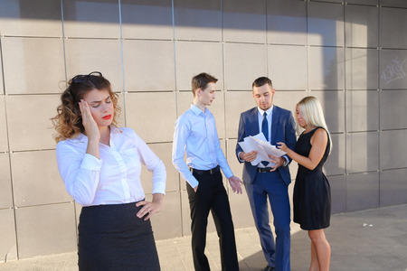 work took: Pretty young perspective business woman, student holds on head from fatigue, rests, took break from work, holds paper and waving them, watching and stands on background of colleagues who discuss workflows, consider paper near of business center on street.