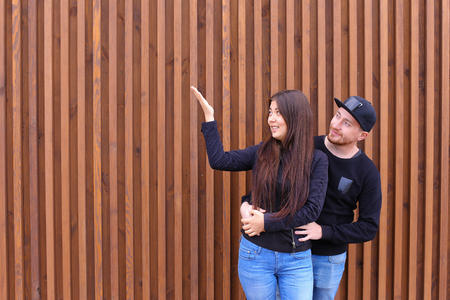 Bride and groom embracing each other, looking to sky and come up forms of clouds, dreaming about future together, enjoy each others arms, will not hurry and rest, stand near wooden walls of restaurant outdoors. Man dressed in black sweater, blue jeans, sn