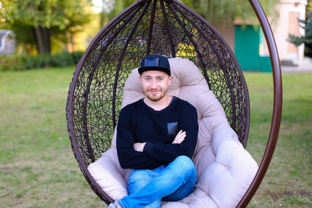 Modern male man waiting for meeting with loved one or friends, come to meeting, decided to relax in restaurant on nature, promotes menswear line. Guy dressed in black sweater, blue jeans, black sneakers and cap and sits in chair park outdoors. Concept of