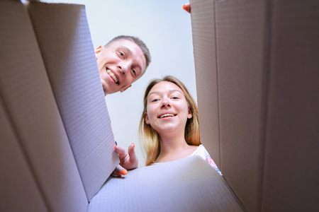 Friends Man and Woman Torn Cardboard Box Lookinginward and Smiling. Recipient Female of European Appearance With Blond Hair and Wide Smile and Recipient Male of European Appearance With Blond Hair and Black T-Shirt Receive Parcels From Relatives of Other  Stock Photo