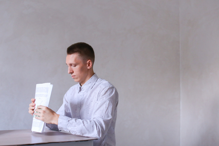 adds: Entrepreneur adds documentation and completes work day. Men with short hair and blond hair sitting on chair at white table in office and dressed in white classic shirt. Concept of businessman office work, sedentary routine work documentation, successful y Stock Photo