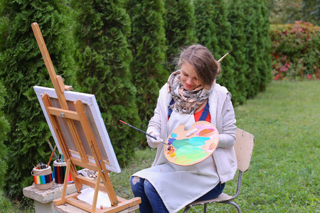 Pretty attractive artist begins to or finishes drawing sitting right in front of to photographer and behind wooden easel, holds palette smeared in paint in large green park day outdoors.Girl with brown hair collected in beam dressed in light jacket, red j
