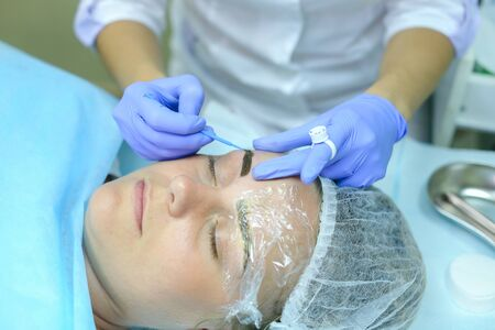 Master of mikrobleyding young attractive girl evaluates correct execution of work, check with help of special device density of drawing and color of hairs of eyebrows, brings to end of last stage in bio tattooing eyebrows. Master dressed in white robe, bl