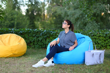 Good-looking girl looking away and resting from city bustle in blue soft and comfortable chair, sitting with flat back in full height directly to camera, poses for photo on background of green plants outdoors in park sunny day. Girl of European appearance Stock Photo