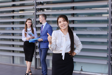 work took: Attractive young perspective business woman, student rests, took break from work, watching, smiling and posing at camera, enjoys success, shows gesture of thumbs up, stands on background of colleagues who discuss workflows, consider paper near of business