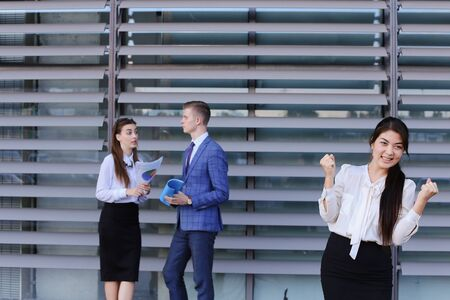work took: Attractive young perspective business woman, student rests, took break from work, watching, smiling and posing at camera, enjoys success, shows gesture Yes! and stands on background of colleagues who discuss workflows, consider paper near of business ce Stock Photo