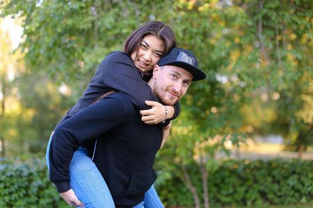 brincando: Pair of young fool around and have fun, fall into childhood and fun leisure time together, she rides guy in love joking and laughing, posing for camera in beautiful large green park outdoors. Man dressed in black sweater, blue jeans and black cap, girl wi Foto de archivo