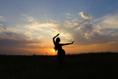 Female with beautiful figure takes yoga postures, gymnastics and ballet spends stretching and meditating, posing for advertising shoot fitness studio, healthy energy drink, dancing belly dancing among wide field on background of yellow sunset and beautifu Stock Photo
