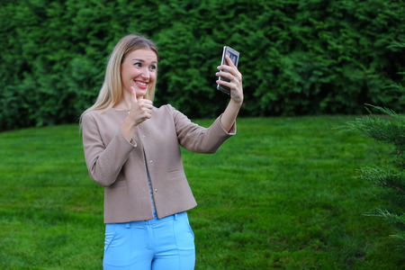 background skype: Active female blonde calls up and talking on Skype, waving and smiling companion to your phone, make selfie, reported good news, and shows emotion gestures. Girl with long hairdressed in bright blouse, beige jacket and blue pants, standing on background o Stock Photo