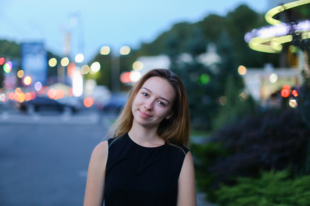 broadly: Young cute girl with light brown hair smiles broadly at camera, removed for advertising of cosmetics or clothing catalog, awaiting meeting with friend and stands against background of glowing lights urban roads outdoors. Girl dressed in black T-shirt and