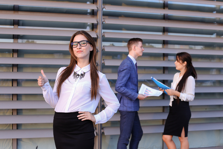 work took: Attractive young perspective business woman, student rests, took break from work, watching, smiling and posing at camera, enjoys success, shows gesture Yes! and gesture of thumbs up, holds on head from fatigue and stands on background of colleagues who
