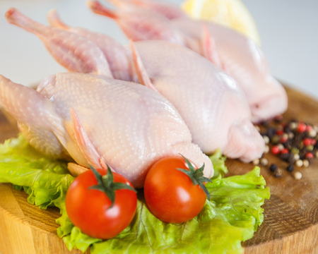 Cleaned and ready to cook fresh raw whole quail with cherry tomatoes, lettuce green leaves, half lemon and pepper pea on circular wooden board on white background. Concept of raw fresh produce and meat, initial etam in cooking and ingredients, master chef