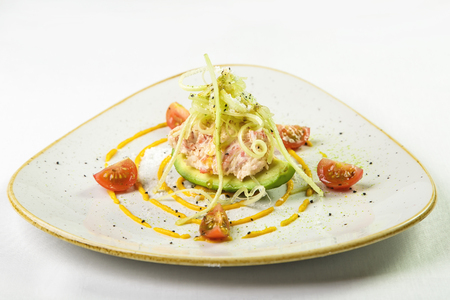 Appetizer before main course of avocado which minced shrimp on top decorated with thin strips of cabbage and onions and sprinkled with cheese sauce and decorated with yellow circle with cherry tomatoes on triangular plate with smooth edges blue with gold  Фото со стока