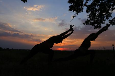 Graceful Mädchen tut sich und meditieren, entspannen und in Ton Körper, Werbung für Yoga-Studio bringen und in Fitness im Freien gegen schönen Himmel und Sonnenuntergang in weiten Feld tätig. Mädchen mit schulterlangen Haaren in rosa Top und schwarze Leggins gekleidet,