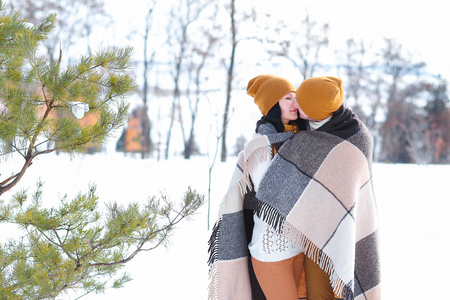 Girl and guy european appearance hugsand kisses in winter white snow. Young couple man and woman love each other, show their sincere feelings. Concept of happiness, happy family life and love.