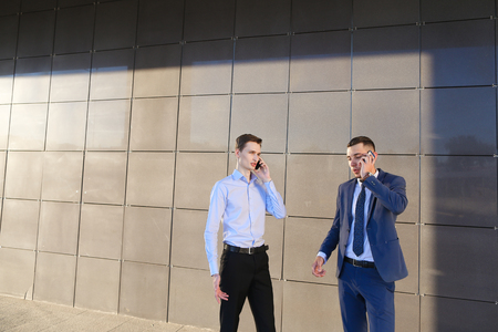 goodly: Two goodly active confident young male men, businessman, students talking on phone, solve important questions, make plans, arranging meetings and stand on background wall of modern business center outdoors. One of guys dressed in blue classic suit, white
