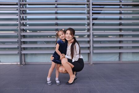 Charming modern female woman, young mother, successful business woman squatted down next to daughter, smile at each other, hug with girl, small child hugging her mother's neck and kisses on cheek, posing for camera, girl holding baby girl on background of
