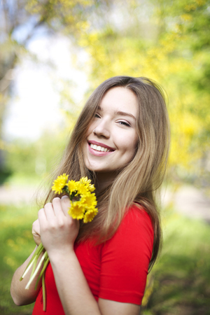 Close portrait of girl with dimples, smile and looks at camera with long blonde hair. Woman lit with happiness, health and beauty in red dress outside in summertime with flowers. Concept of happy life.