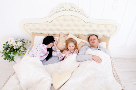 Young couple with baby girl female lying and talking in white bedroom, on bed. Luxury furniture and beautiful interior in bright colors. Mom with black long hair, Dad European appearance, daughter with long white hair smiling. Concept of happy family rela Stock Photo