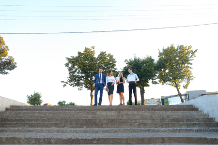 Young modern confident people, two boys and two girls, perspective entrepreneurs, students smiling, hold in hands gadgets, tablet, smartphone and papers, documents, go down stairs outdoors. One of guys dressed in blue classic suit, white shirt with tie, s