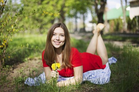 Close portrait of girl with dimples, smile and looks at camera with long blonde hair. Woman lay on green grass picnic, lit with happiness, health and beauty in red dress outside in summertime with flowers. Concept of happy life.