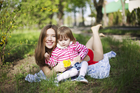 Close portrait of girl with kid baby and dimples, smile and looks at camera with long blonde hair. Woman lay on green grass picnic, lit with happiness, health and beauty in red dress outside in summertime with flowers. Concept of happy life. Stock Photo