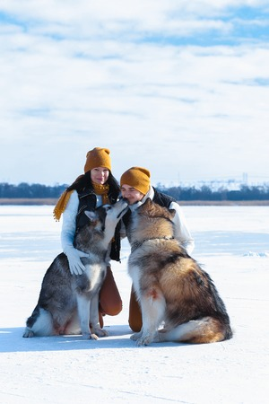 Girl and guy european appearance hugs in winter white snow. Two dogs are playing outside. Young couple man and woman love each other, show their sincere feelings. Concept of happiness, happy family life and love. Stock Photo