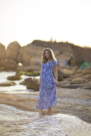 Young woman came to rest to sea coast. Girl walk smile dressed in long dress, European appearance. Concept female beauty, enjoy life in travel and tourism in the town.