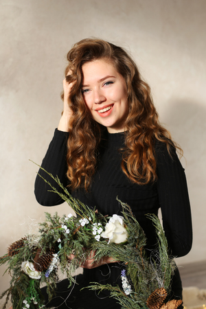 Close portrait of girl with beautiful smile with dimples and curls on blond hair. Woman holds wreath or floral arrangement. Concept of happiness, carefree, beauty, and shampoo ads, solar fun-filled day. Stock Photo